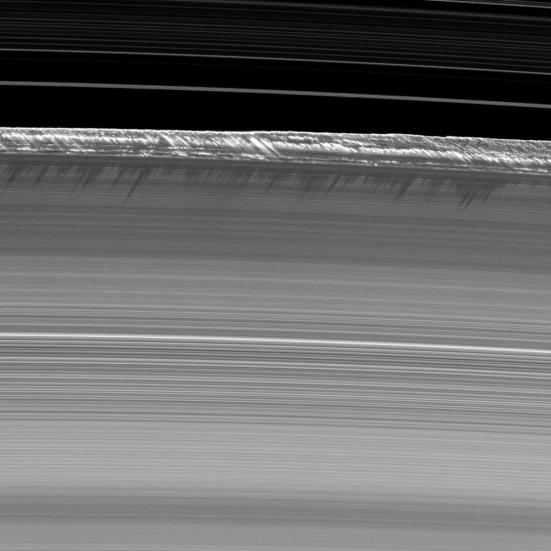 """Vertical structures, among the tallest seen in Saturn's main rings, rise abruptly from the edge of Saturn's B ring to cast long shadows on the ring in this image taken by NASA's Cassini spacecraft two weeks before the planet's August 2009 equinox."""